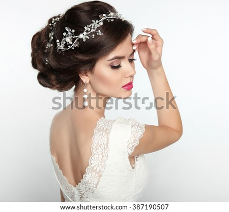 Wedding Hairstyle. Beautiful fashion bride girl model portrait. Makeup. Luxury jewelry. Attractive young woman with brown curly hair styling - stock photo