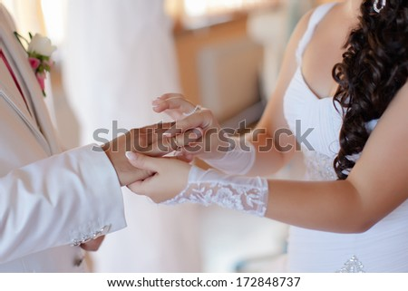 Wedding hands. Bride puts on a wedding ring to a groom - stock photo