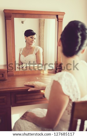 wedding: Happy beautiful brunette bride sitting on chair and looking through mirror - stock photo