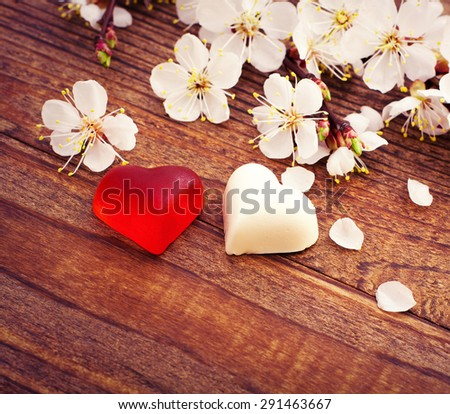 Wedding hearts. Spring. Flowering branch with white delicate flowers on wooden surface. - stock photo