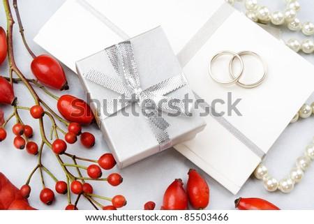 Wedding invitation with wedding rings, gift box, decorative wild roses and rowan. Still life. - stock photo