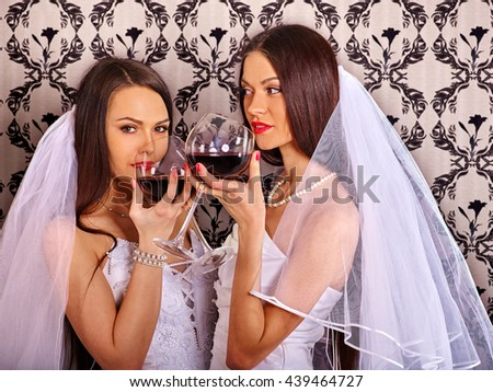 Wedding lesbians girl in bridal dress drinking red wine. Alcohol on lesbian wedding. Wallpaper background. - stock photo