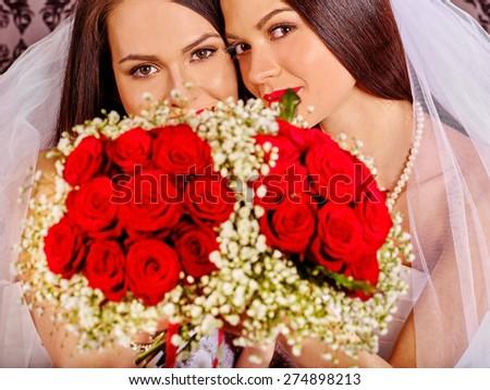 Wedding lesbians girl in bridal dress holding  flower bouquet.  - stock photo