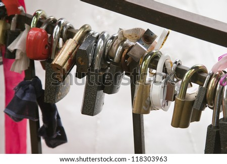 Wedding locks on the rail of a bridge - stock photo