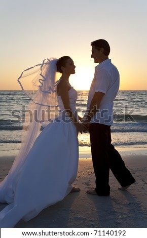 Wedding of a married couple, bride and groom, together at sunset on a beautiful tropical beach - stock photo