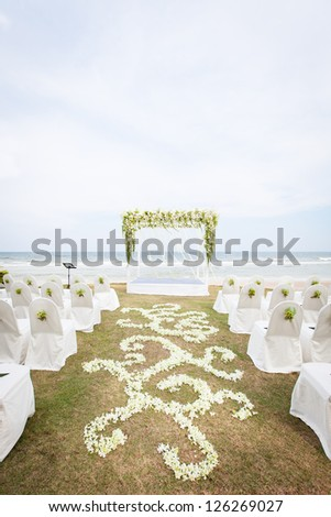 Wedding on the beach. A beautiful wedding arch, decorated with flowers, chairs for guests, floral pattern of white orchids on the green grass against the sea and sky. - stock photo