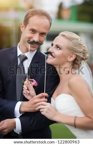 Wedding on the nature. couple in love bride and groom with a bouquet at bridal day in summer. Enjoy a moment of happiness and love and having fun with funny false mustache. playful newlywed family - stock photo