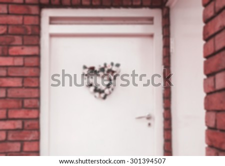 Wedding (or birth) flower wreath in heart shape on door. London, UK. Aged photo. Black and white. Blurred retro aged photo. - stock photo
