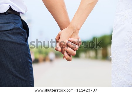 Wedding photo of married couple holding hands - stock photo