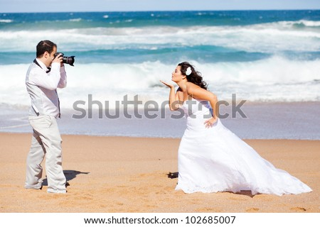 wedding photo shoot - groom taking bride's photo - stock photo