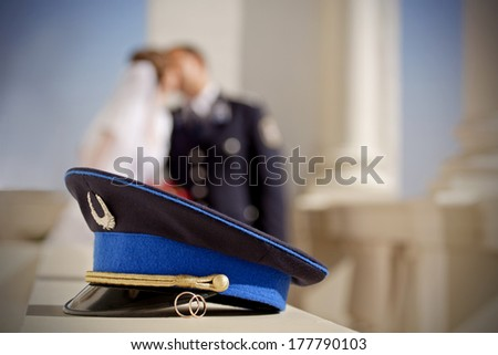 wedding photo with rings and police or military officer hat - stock photo