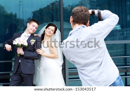 Wedding photographer in action, taking a picture of the bride and groom - stock photo
