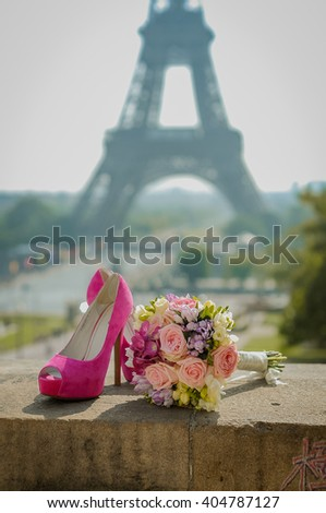 Wedding pink shoes and wedding bouquet under the Eiffel Tower in Paris, France - stock photo