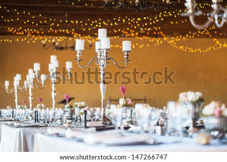 Wedding reception hall with decor including candles, cutlery and crockery; selective focus on candelabra - stock photo