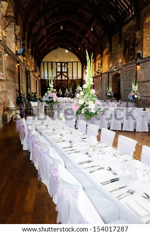Wedding reception table decoration showing flower arrangement and silver cutlery - stock photo
