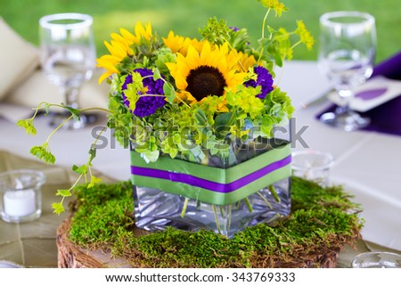 Wedding reception tables are decorated with flower centerpieces for a beautiful natural look. - stock photo