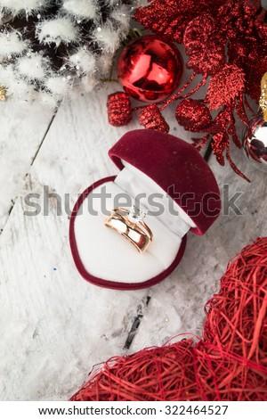 Wedding ring among Christmas decorations on wood background. - stock photo