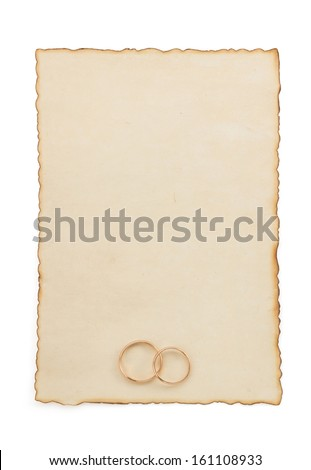 wedding ring and aged paper isolated on white background - stock photo