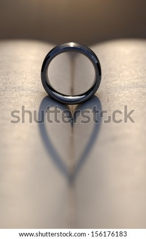 Wedding ring between the pages of an old book with the sunlight casting a heart shaped shadow. - stock photo