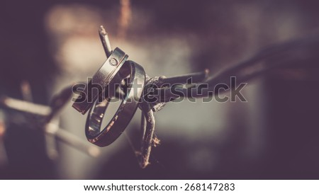 wedding ring hanging on barbed - stock photo