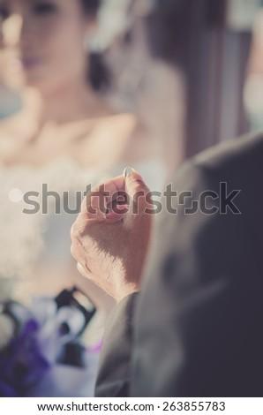 Wedding ring in groom hand. - stock photo