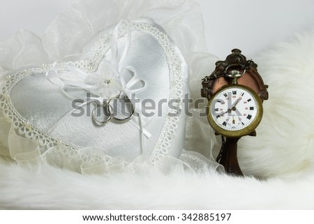 wedding ring on heart pillow, clock on soft fabric background - stock photo