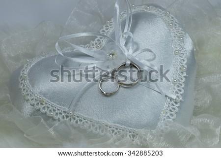 wedding ring on heart pillow, soft fabric background, still life, wedding symbols - stock photo