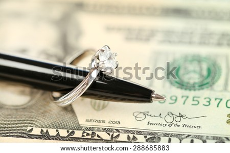 Wedding ring on pen, on banknotes background. Marriage of convenience - stock photo