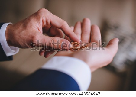 Wedding ring on the hand of man groom - stock photo