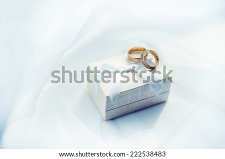 Wedding rings an the box on the background of white textile - stock photo
