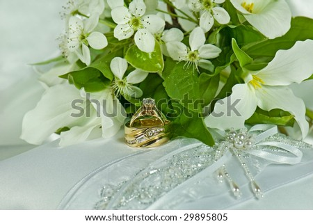 wedding rings and bouquet on pillow - stock photo