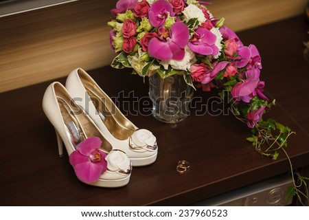 wedding rings and bride's shoes on the desk - stock photo
