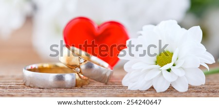 wedding rings and flower on wooden board - stock photo