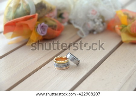 Wedding rings and flowers bouquet - stock photo