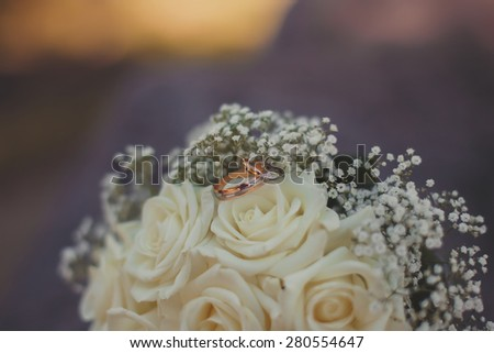 Wedding rings and flowers. Close up. - stock photo