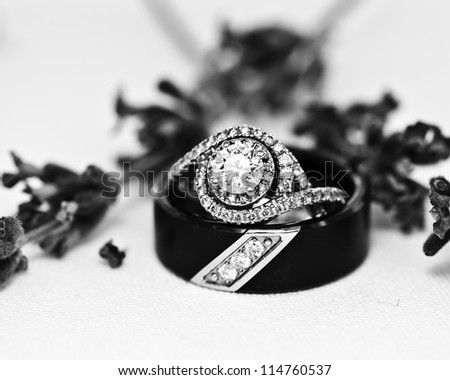 Wedding rings and flowers on lace table cloth - stock photo