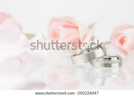wedding rings and pink roses  - stock photo