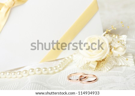 Wedding rings and wedding invitation with bow - stock photo