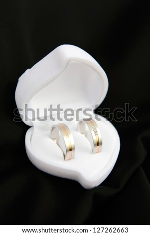 Wedding rings and white heart on wedding jacket in portrait photo orientation, focused to the rings - stock photo
