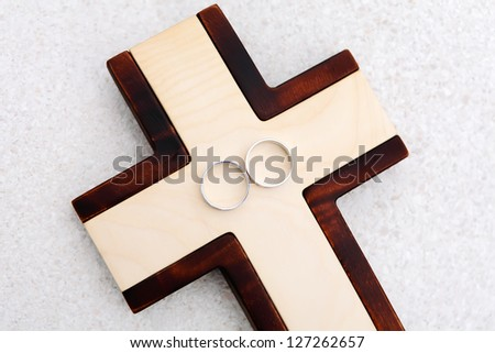 Wedding rings and wooden cross with white stone background, landscape photo orientation, focused to rings - stock photo
