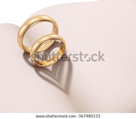 Wedding rings casting heart shaped shadow over a blank book - stock photo