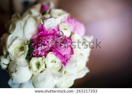 Wedding Rings Close up with Cute Flower ranunculus bouquet. Rustic Style decoration. Selective focus. Shallow DOF.  - stock photo