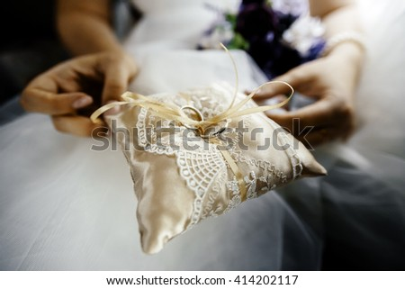 wedding rings for the newlyweds in the hands on silk pillow - stock photo