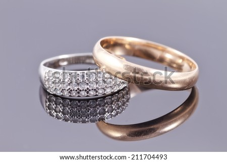 Wedding rings : gold and silver with precious stones. On a black reflective surface - stock photo