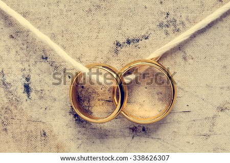 Wedding rings hanging on rope. Vintage image. - stock photo