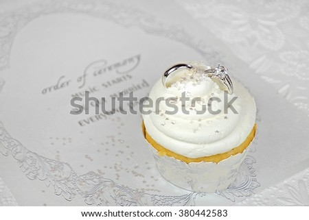 wedding rings in cupcake icing on contemporary wedding invitation - stock photo