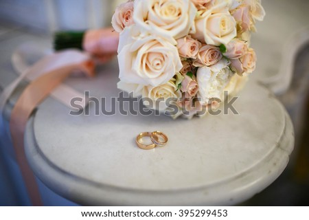 Wedding rings lie on a marble table. In the background is a wedding bouquet of roses - stock photo