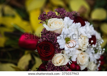 wedding rings lie on a wedding bouquet of red and peach - stock photo