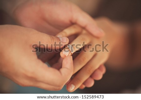Wedding rings. Man giving an engagement ring to his girlfriend. Boyfriend Surprised Her Girlfriend With Engagement Ring In Restaurant - stock photo