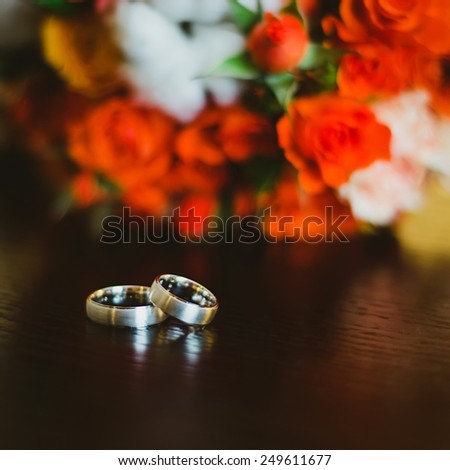 wedding rings near red flowers - stock photo
